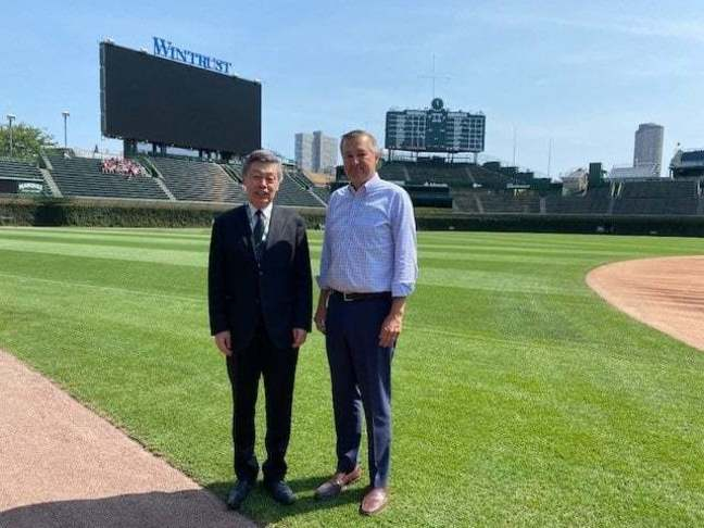 CG Okada and Tom Ricketts standing in Wrigley Field, Chicago