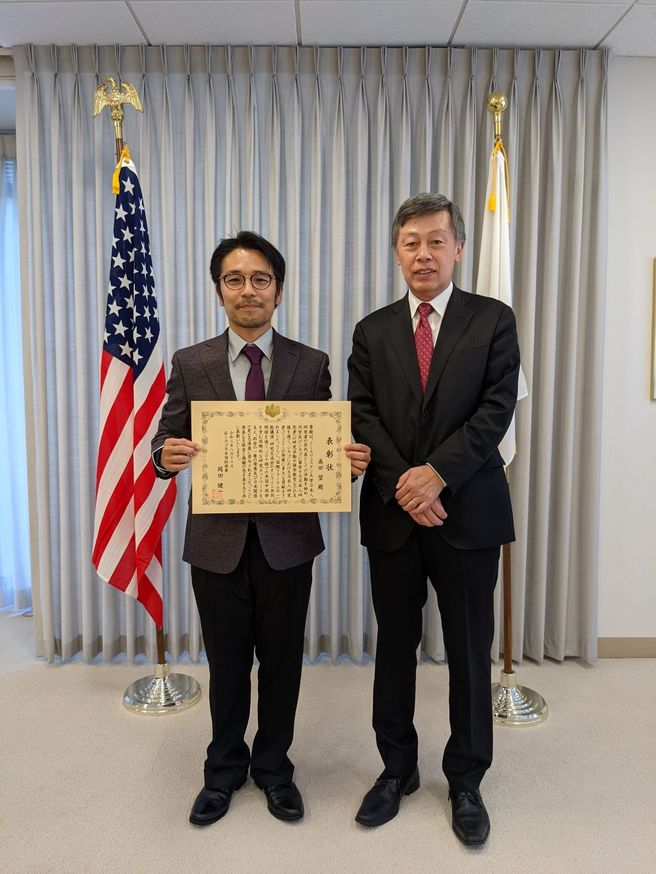 Dr. Takata and CG Okada (left to right) stand between the US and Japan flags while Dr. Takata poses with the CG Commendation diploma