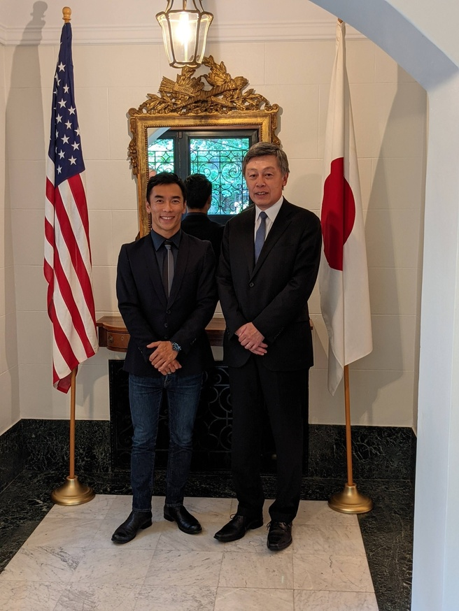 Takuma Sato and CG Okada (left to right) standing between the US and Japan flags in the foyer of the Official Residence
