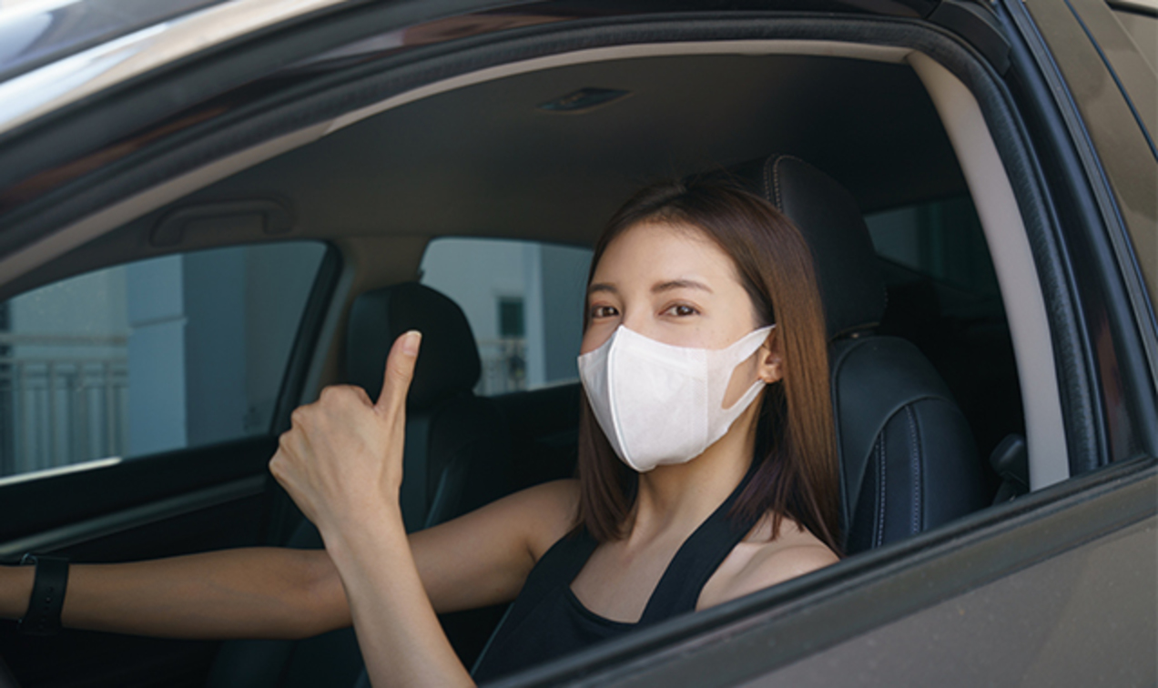 A masked woman giving a thumbs up from her car