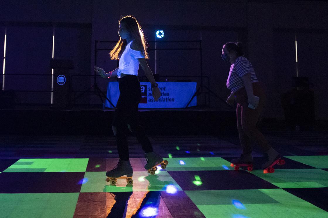 Students skating in black neon lighting