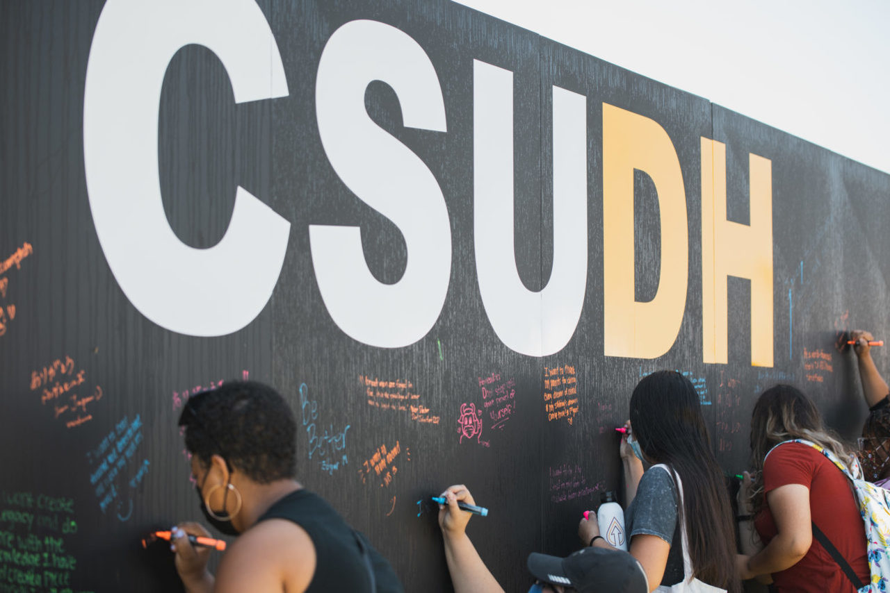Students signing wall at New Student Convocation
