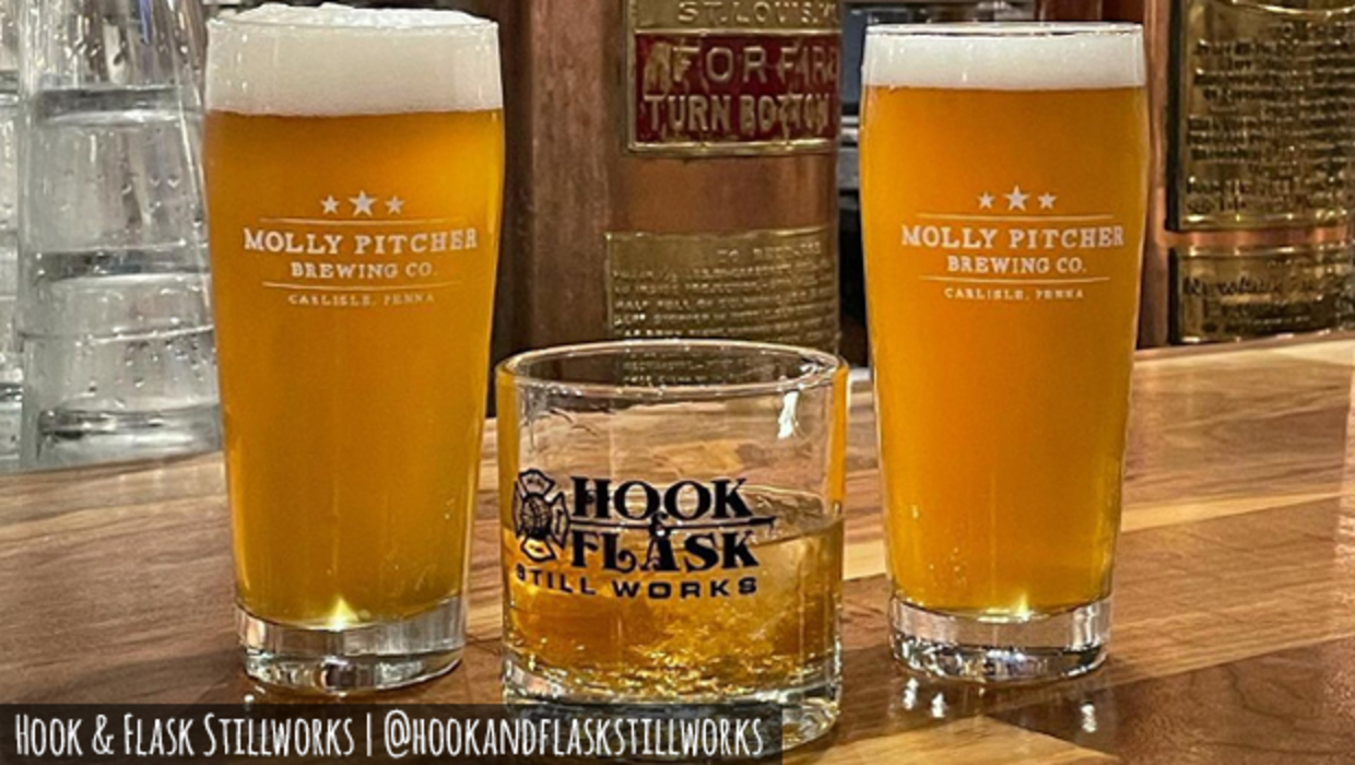 A rustic bartop with two tall glasses of Molly Pitcher Brewing Company draft beer sit beside a glass of Hook & Flask whiskey on the rocks.