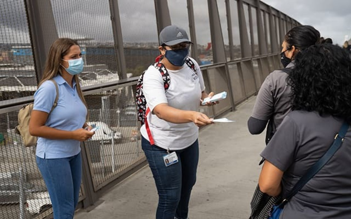 Project 2VIDA! research assistants Josefina Pavez (left) and Raquel Rocha (right) hand out fliers for a pop-up vaccination clinic near the U.S.-Mexico border.