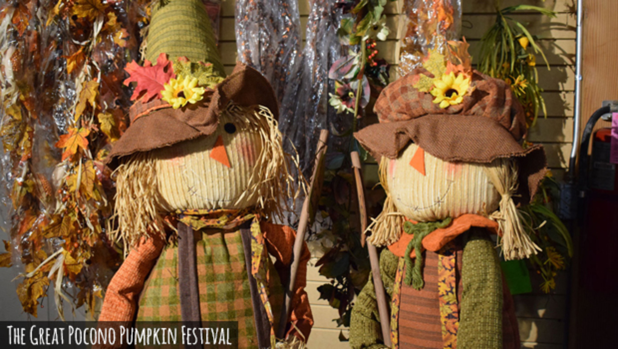 A pair of country-crafted decorative scarecrows smiling to great visitors of the Great Pocono Pumpkin Festival