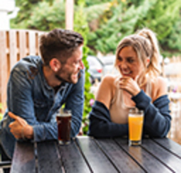 A couple enjoying craft brews at an outdoor table
