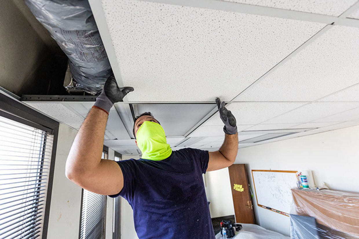 A worker replaces damaged ceiling tiles at School of Public Health and Tropical Medicine's Tidewater Building.