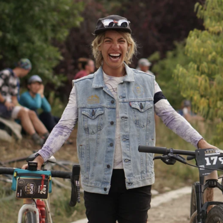 Sarah Sturm smiling big and holding her racing bikes