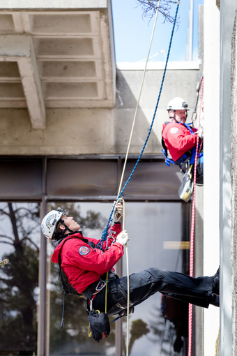 Two rescue team members rappel down Evans Hall
