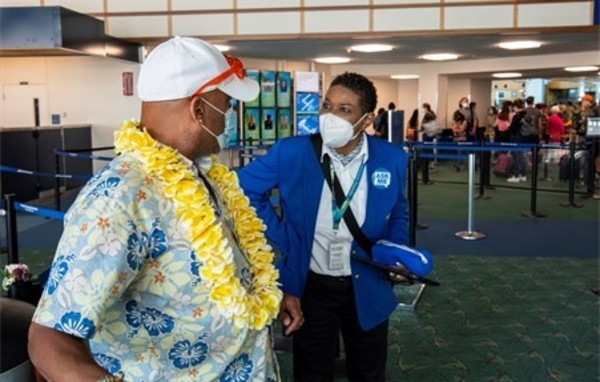 ABM employee assisting a traveler who is wearing a tropical shirt and yellow lei.