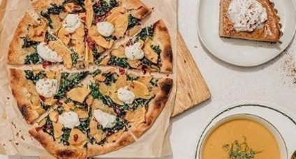 Butternut squash soup, pizza and pumpkin pie on table