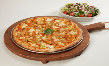 Buffalo chicken pizza being pulled from a coal oven