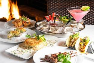 A table full of plates of food including oysters and tacos and a pink martini drink