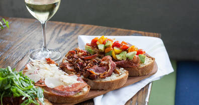 Table with three kinds of bruschetta and a glass of white wine