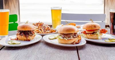 Hamburgers, fries and beers on a table
