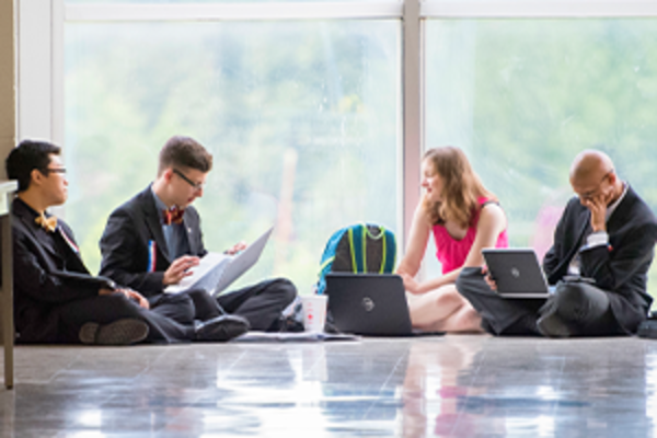 Four students in business attire sit on the floor in front of massive windows.