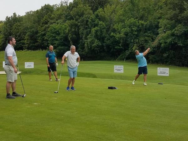 Attendees at the golf event in action on the golf course.