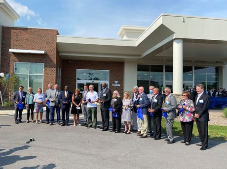 Ribbon-cutting photo in front of the new buidling.