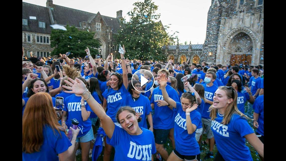 Students wearing Duke blue t-shirts throwing confetti in front of the Chapel.