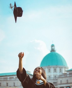 College graduate throwing cap into the air