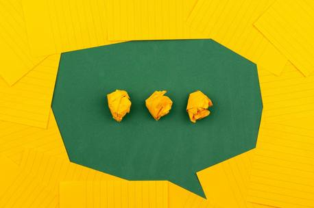 A green speech bubble on a yellow background with yellow ellipsis inside the speech bubble