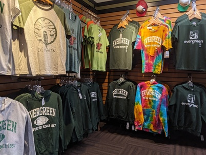 Hanging t-shirts and sweatshirts with various Evergreen branding, including a tie dye hoodie