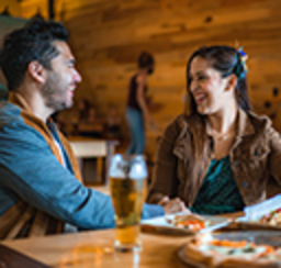 A couple converses over a glass of beer in a rustic pub setting