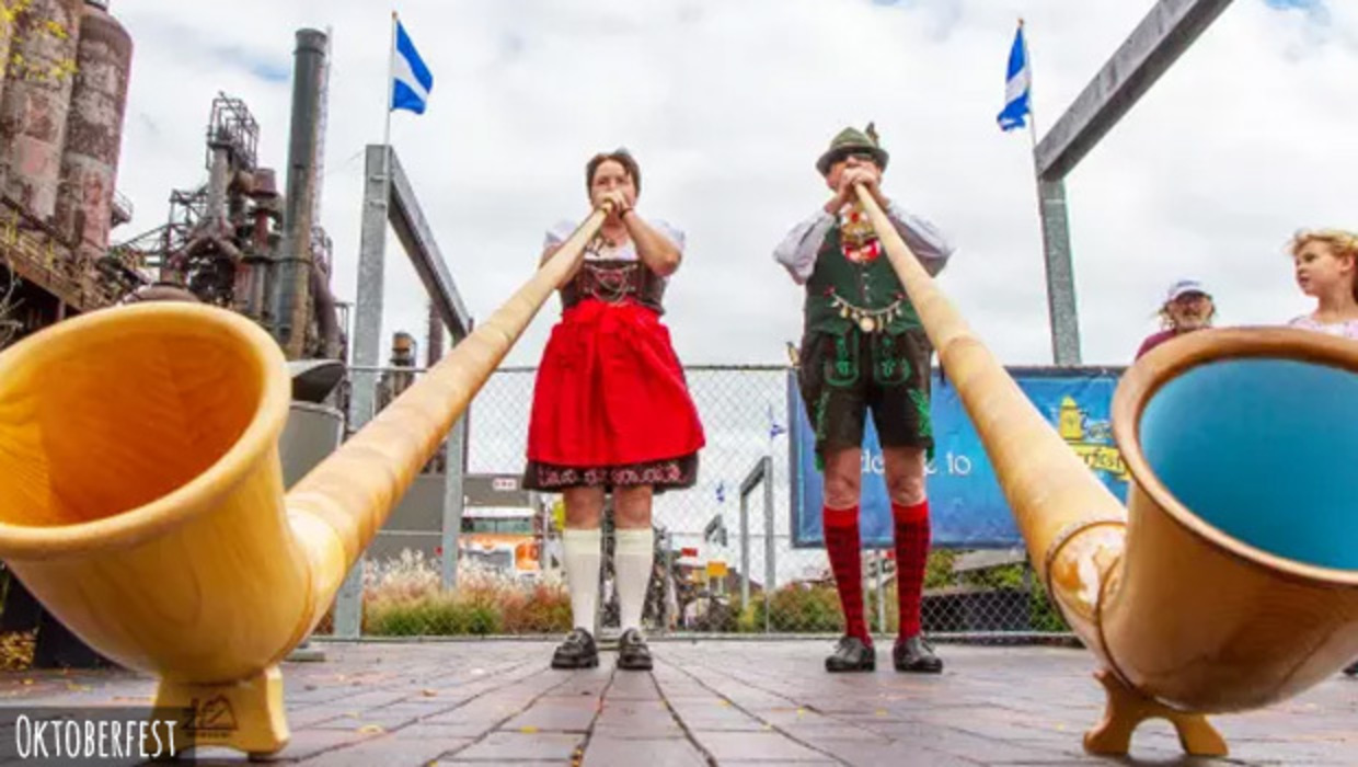 Performers in tradtional german outfits play giant apline horns with Bethlehem's Steel Stack in the background