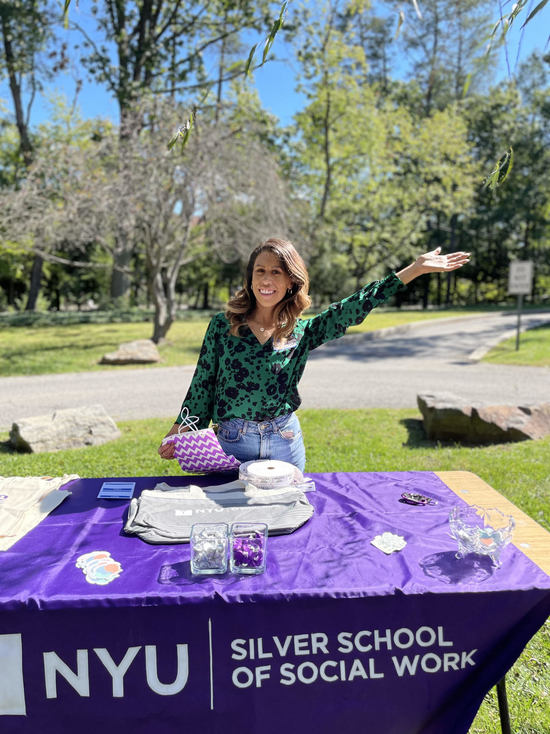 Michelle Escamilla-Valladares, MSW '22, waves in front of a table full of swag items.