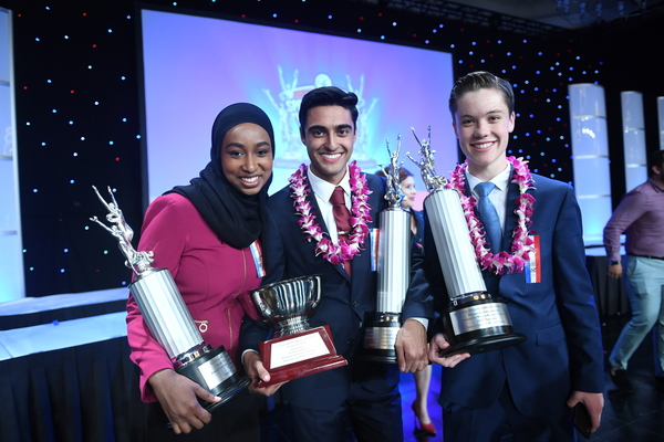 A group of student award winners pose together with trophies